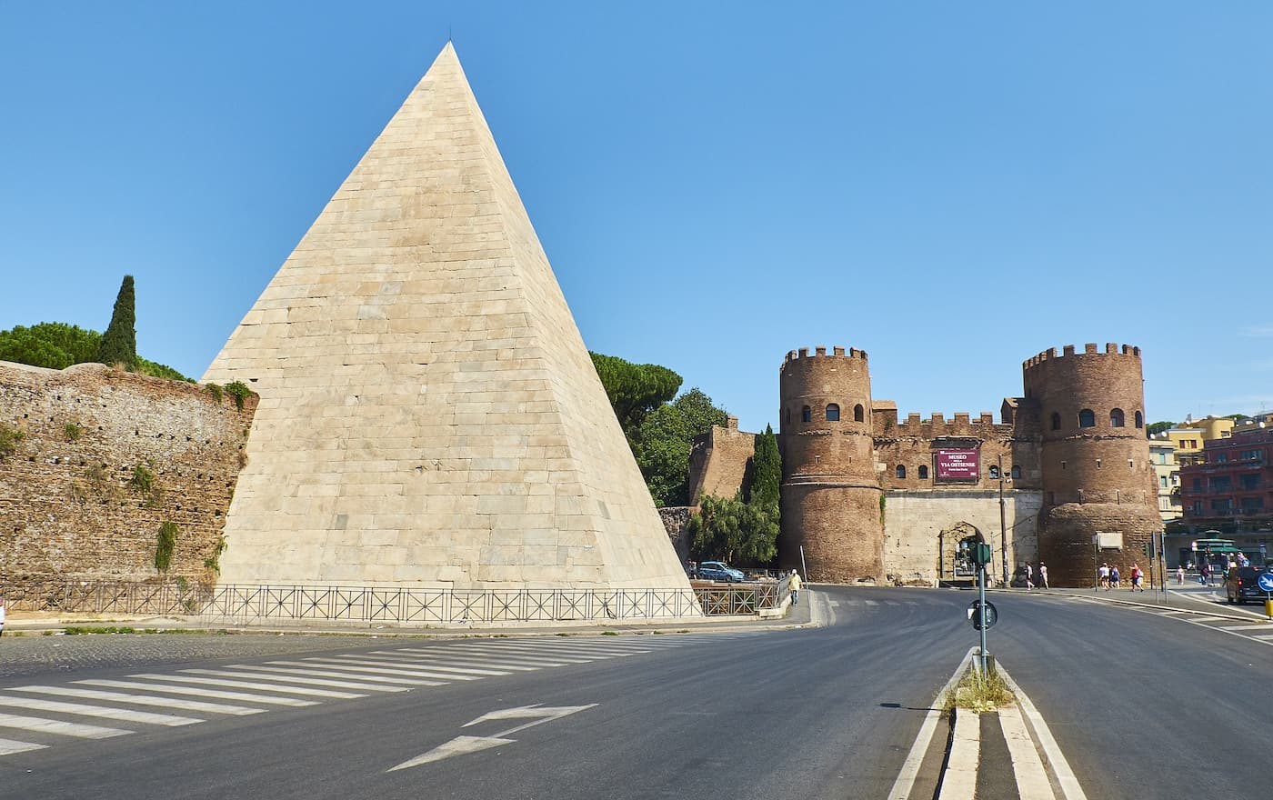 The Pyramid of Cestius and Porta San Paolo gate in background. View from Piazzale Ostiense square.