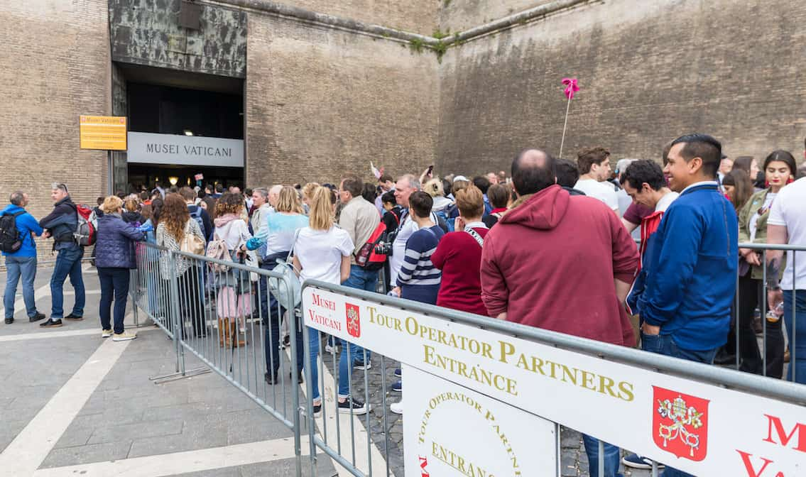 Crowds of tourists wait at the entrance to Vatican Museums